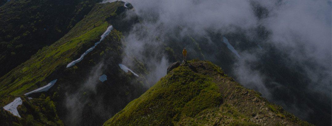 Person steht auf grünem grasbedeckten Hügel