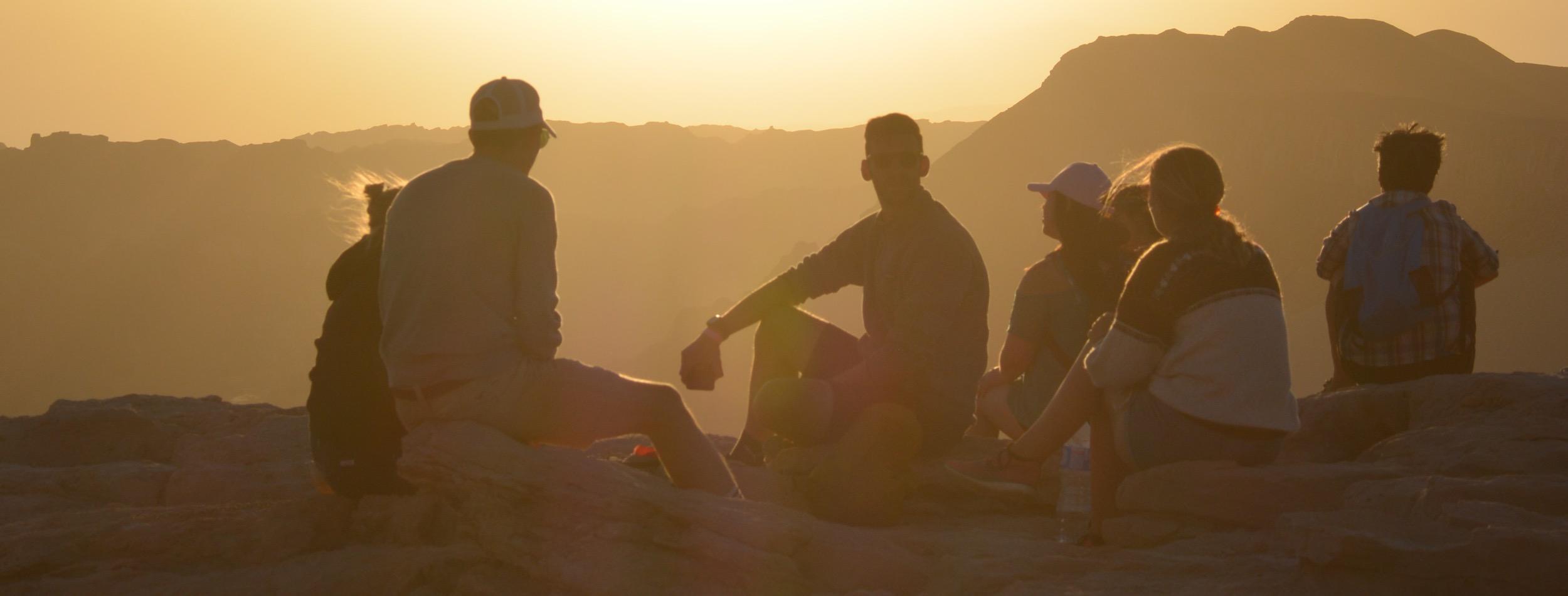 Gruppe von Menschen bei Sonnenuntergang